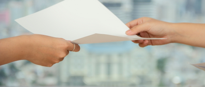 Person handing sheet of white paper to another person