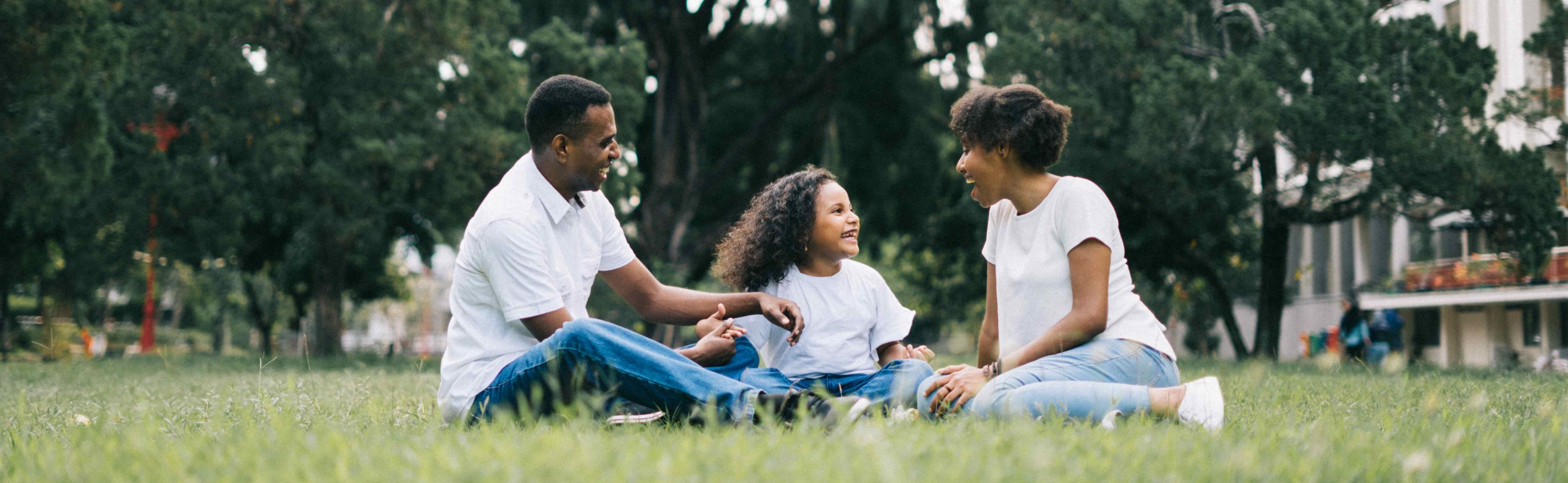 Three person family sitting on grass