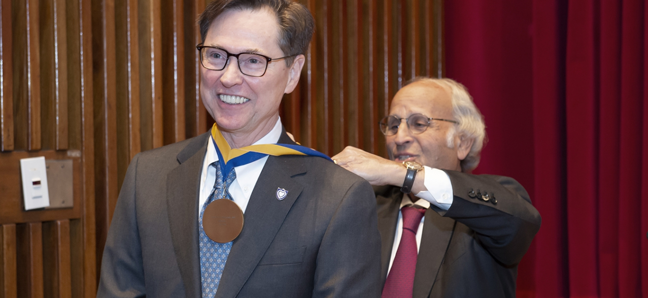 Terence S. Dermody receiving medal from Arthur S. Levine, MD