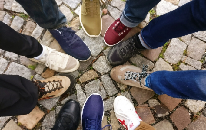 People standing in circle pointing shoes
