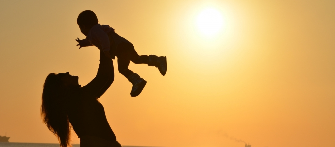 Woman holding baby in air in front of sunset