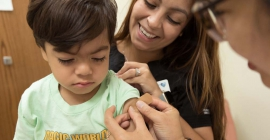 Provider and nurse putting bandaid on child's arm