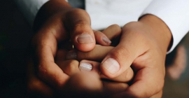 Hands of doctor holding hands of child