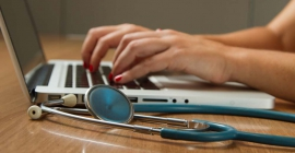 Hands typing on laptop in front of stethoscope