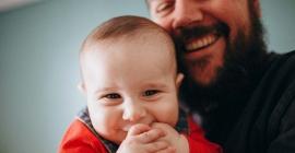 Baby and dad smiling at camera