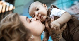 Mom holding baby in air and kissing on cheek