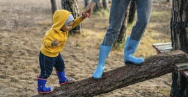 Young boy walking on log while holding hands with adult