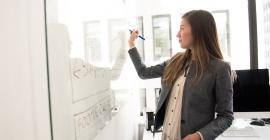 Woman writing on white board