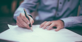 Person signing paper with black pen