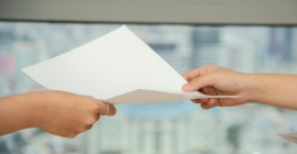 Person handing white sheet of paper to another person