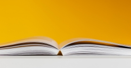 Open book on table with yellow background
